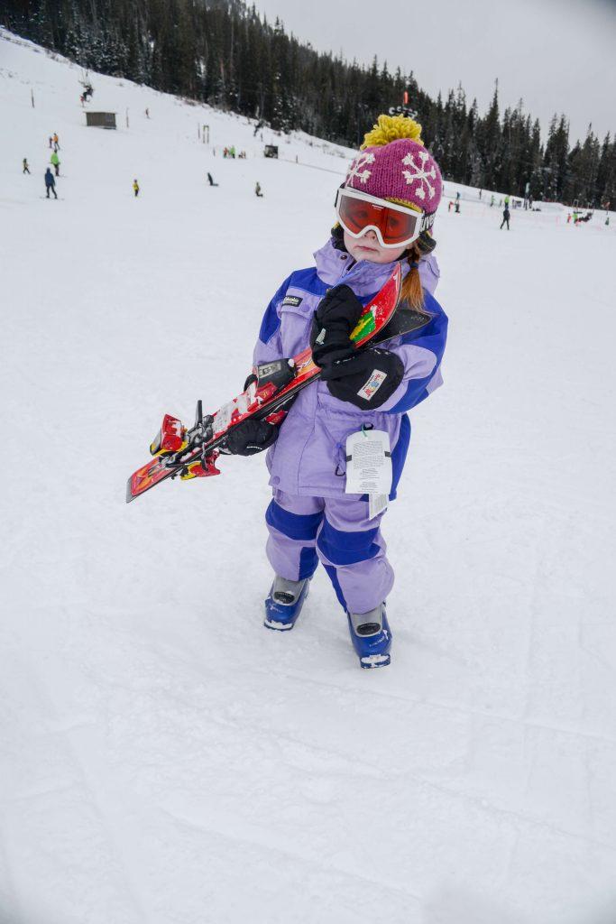 toddler carrying skis