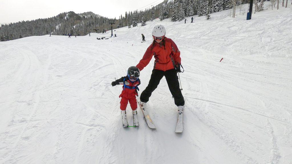 Skiing Kids mom pushing toddler on skis