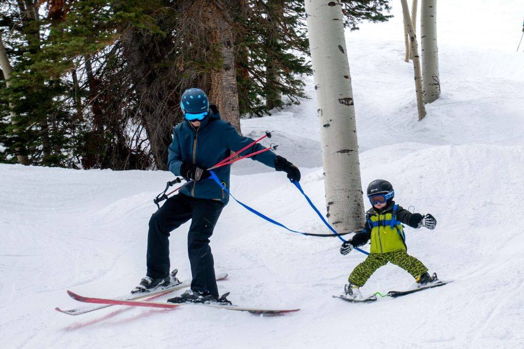 dad and boy skiing with ski harness