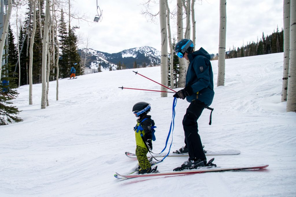 toddler skiing with a ski harness